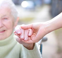 elder woman smiling while holding hands