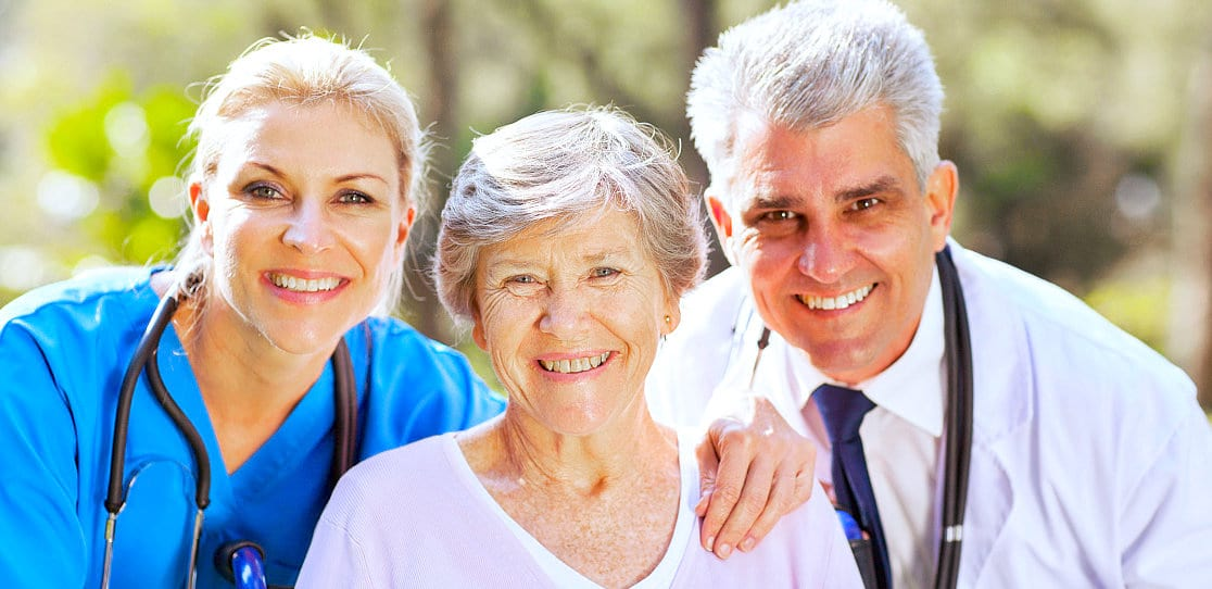doctor and nurse with an elder woman smiling