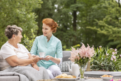 Happy nurse giving tea to elder woman while eating breakfast on the terrace